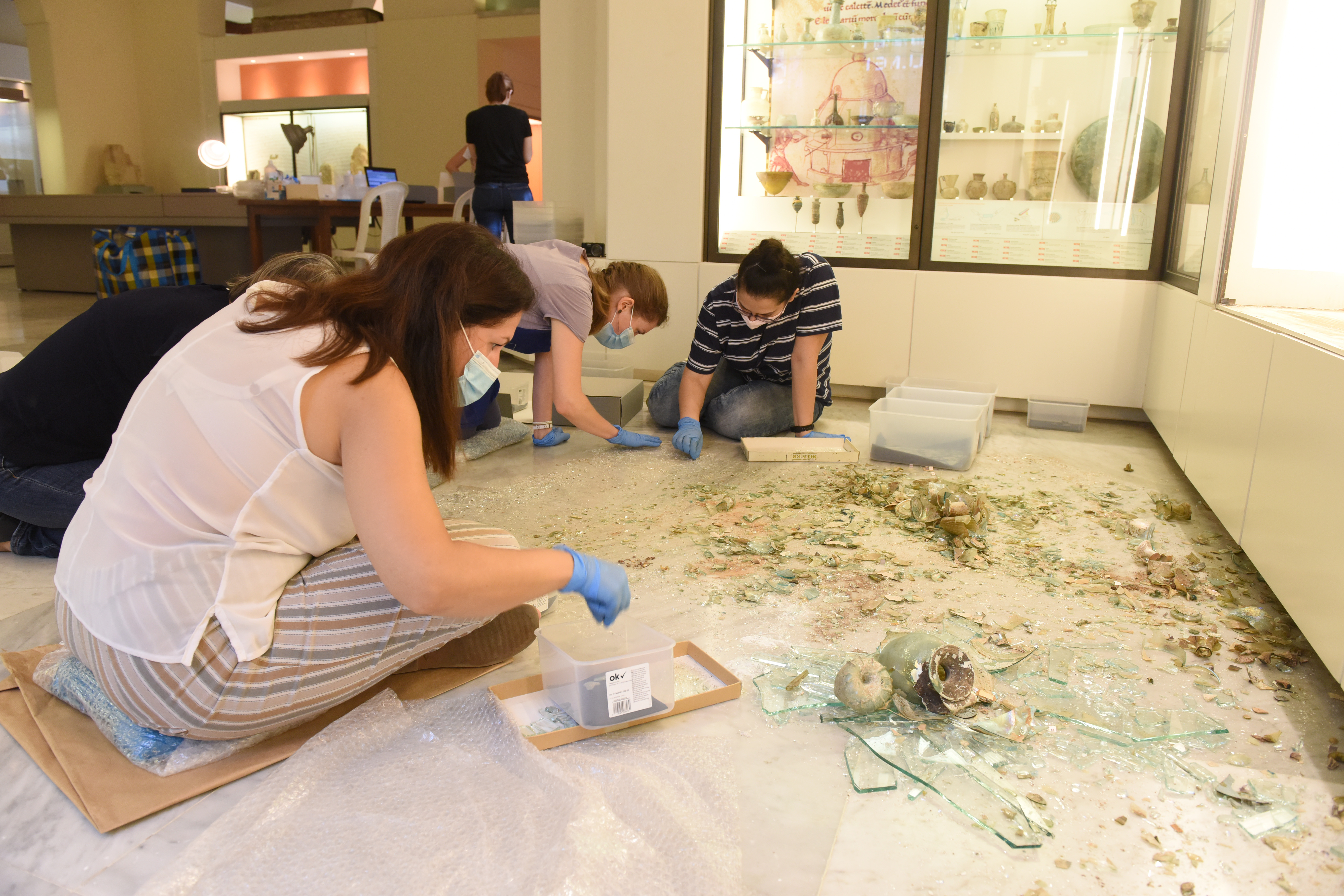 Conservators and student volunteers retrieve fragments of broken glassvessels from amongst the shattered glass from the display case and nearby windows at the Archaeological Museum, AUB. Courtesyof the AUB Office of Communications and Archaeological Museum.