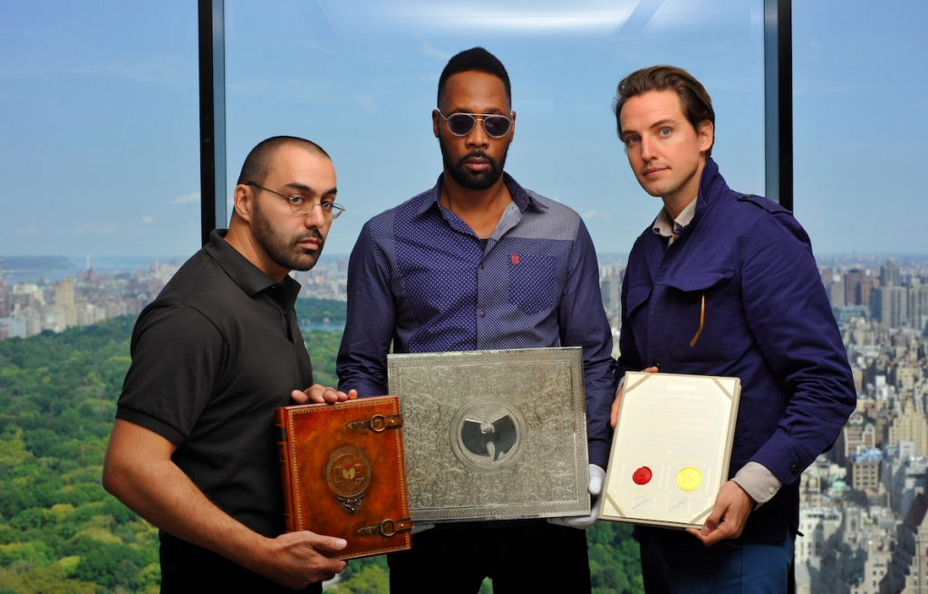 """Wu-Tang Clan members Cilvaringz and RZA and Paddle8 founder Alexander Gilkes hold the book, box, and certification that come with the """"Once Upon a Time in Shaolin"""" album. Photo courtesy of Paddle8."""