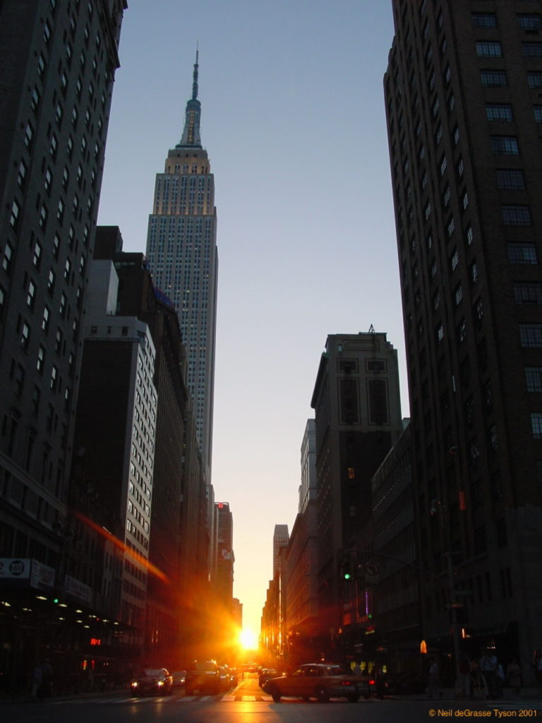 Neil deGrasse Tyson, Manhattanhenge (2001), sunset looking down 34th Street. One of two days when the sunset is exactly aligned with the grid of streets in Manhattan. Photo ©Neil deGrasse Tyson, courtesy of the American Museum of Natural History.