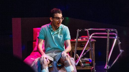 <i>Hi, Are You Single?</i> (2017). Production still from Ryan Haddad's solo play Hi, Are You Single? Photo by Michael Bernstein. Image description: Under cool stage lighting, Ryan Haddad sits at the end of a bed beside his metallic walker. He wears square glasses, a teal polo, patterned shorts, and lower leg braces.