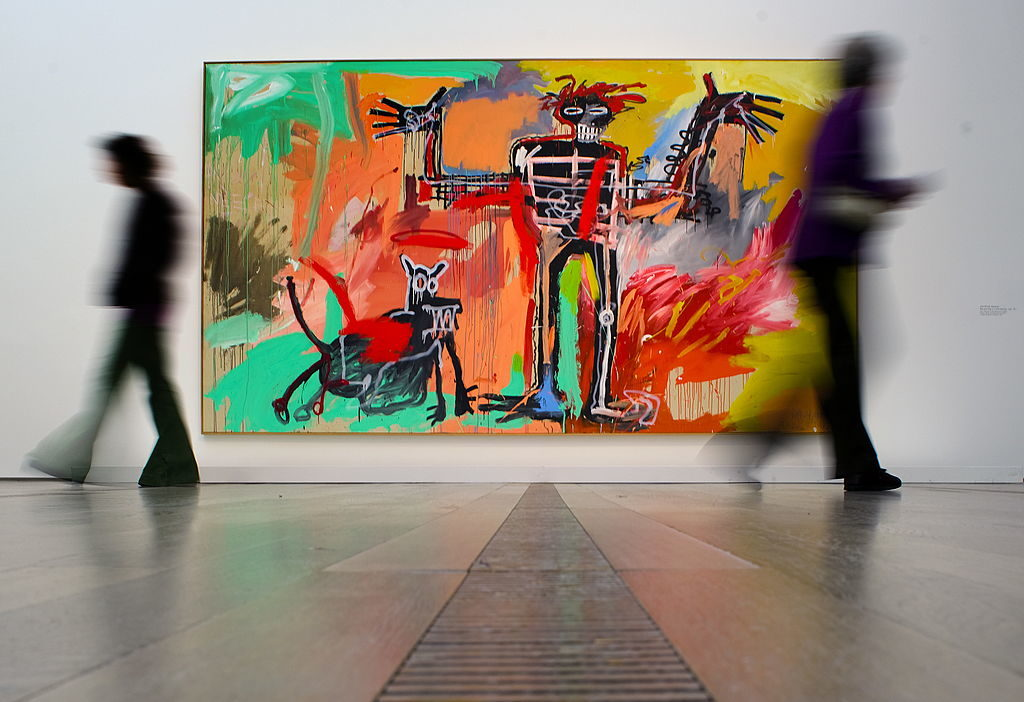 Visitors pass in front of a painting by Jean-Michel Basquiat entitled Boy and Dog in a Johnnypump on May 7, 2010, at Art Basel. Photo: Fabrice Coffrini/AFP/Getty Images.