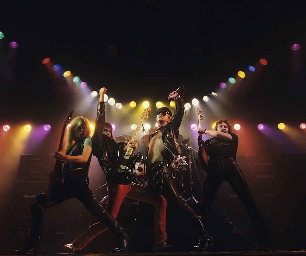 Left to right: K.K. Downing, Glenn Tipton, Rob Halford and Ian Hill of Judas Priest perform on stage - Unleashed In The East album cover session taken in July 1979. (Photo by Fin Costello/Redferns)