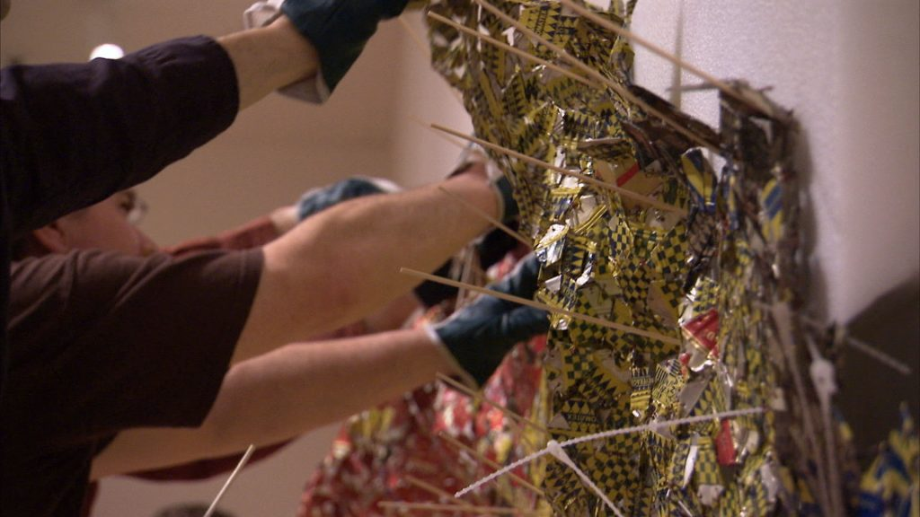 """Studio assistants working on El Anatsui's massive assemblages. Photo: production still from the """"Art in the Twenty-First Century"""" Season 6 episode, """"Change."""" © Art21, Inc. 2012."""