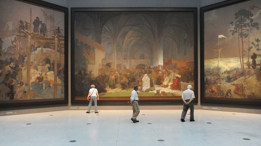 """Visitors look at paintings of the """"Slav Epic"""", a cycle of 20 allegories tracing the history of the Slavic people and inspired in part by mythology, by Art Nouveau Czech artist Alfons Mucha, at the National Gallery in Prague. Michal Cizek/AFP/GettyImages."""