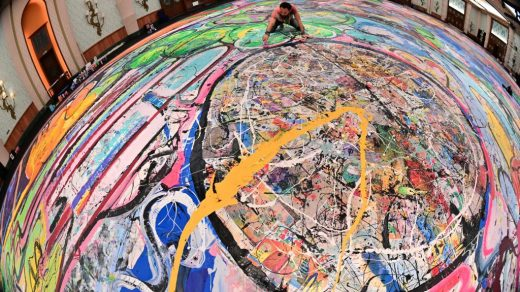 A picture taken with fisheye lens shows contemporary British artist Sacha Jafri working on his record-breaking painting entitled <em>The Journey of Humanity</em> on September 23, 2020, in the Emirati city of Dubai. Jafri spent months of lockdown at the Atlantic, the Palm, hotel due to the pandemic. The painting's $62 million sale will fund health and education initiatives for children living in poverty worldwide. Photo by Giuseppe Cacace/AFP via Getty Images.